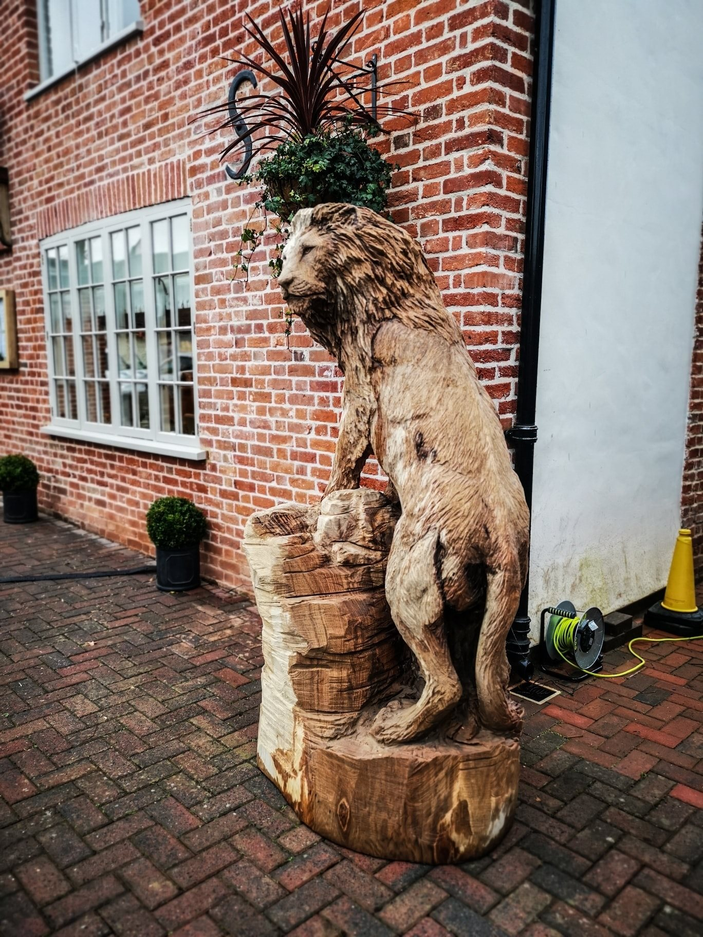 a wood lion sculpture standing on a tree stump outside a red brick building