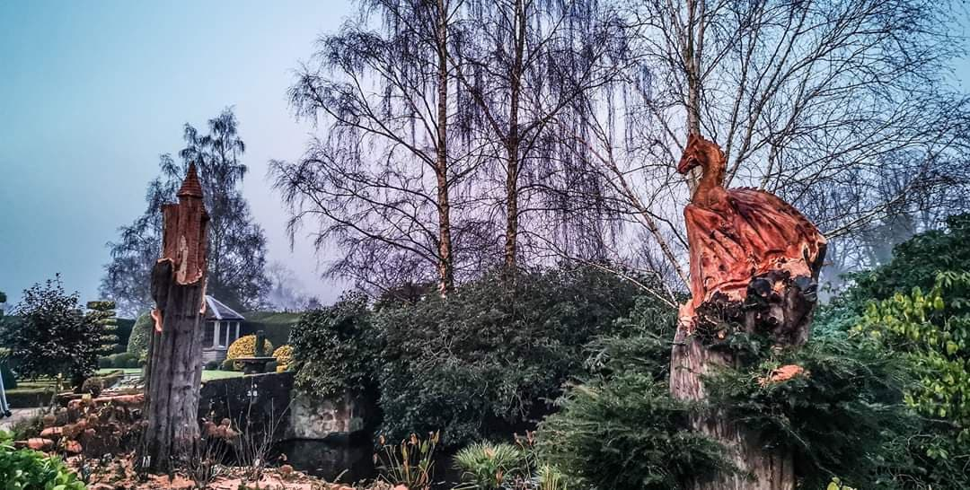 photo shows a garden. One the right is a dragon carved from yew. On the left two fairytale towers also carved from yew. Shown as an example of the fourth best wood for sculpture that will be outdoors.