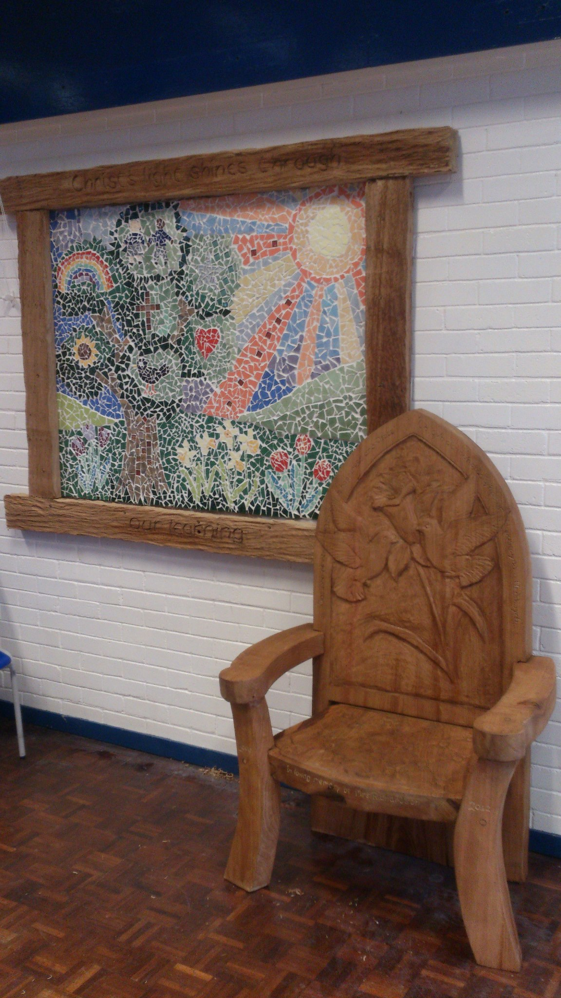 chair with a daffodil carved into the back. to the left is a framed mosaic. it is made of sweet chestnut, the fifth best wood for a sculpture according to simon o'rourke