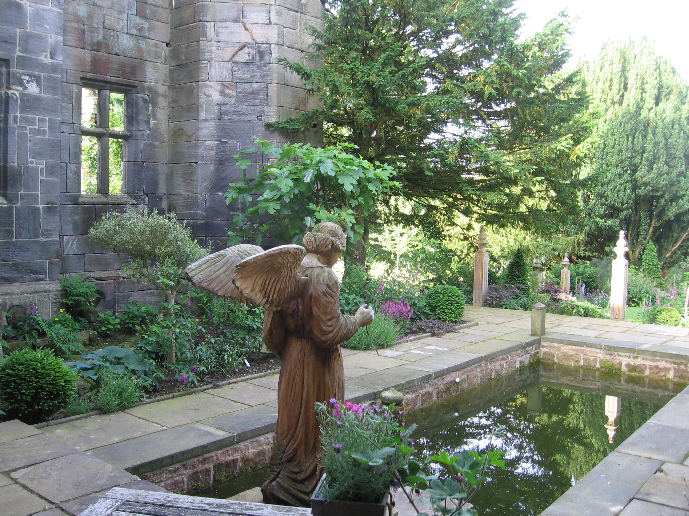What is the best wood for a sculpture? Photo shows a sculpture of an angel in oak standing next to a small pond. The oak is aging and turning a deeper shade of grey, but has no signs of decay.