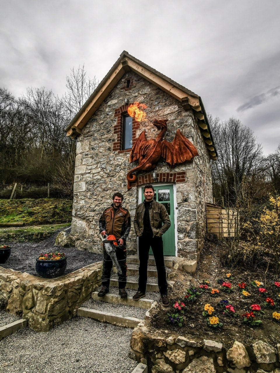 george clark stands next to sculpter simon o'rourke. they are in front of a small brick building with a redwood fire breathing dragon mounted on the wall. the dragon is made of redwood and was one of simon's sculptures of 2020