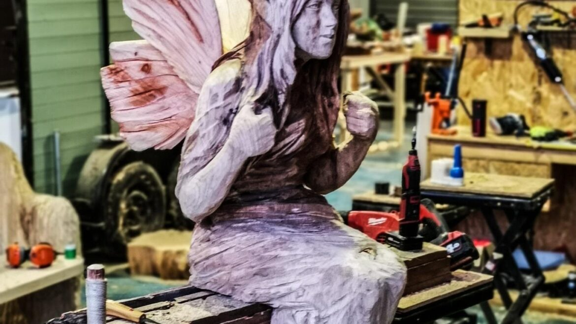 Photo shows a half finished wood sculpture of an elf on a swing; one of Simon O'Rourke's 2021 sculpture commissions