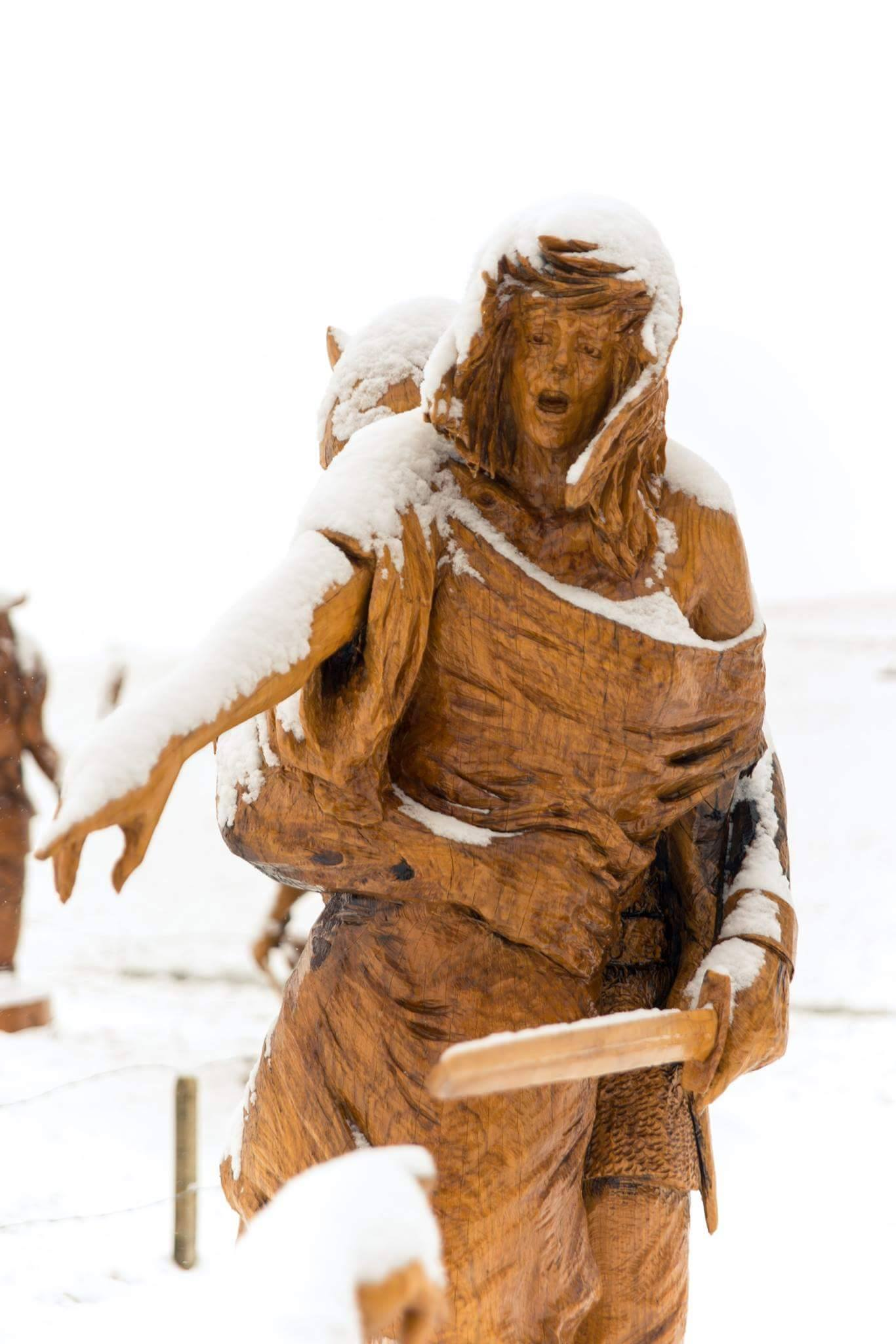 Sculptures in the snow: Viking raid by simon o'rourke. The photo shows a young woman being kidnapped by a viking. The sculptures are topped in snow and the entire landscape is also covered in snow.