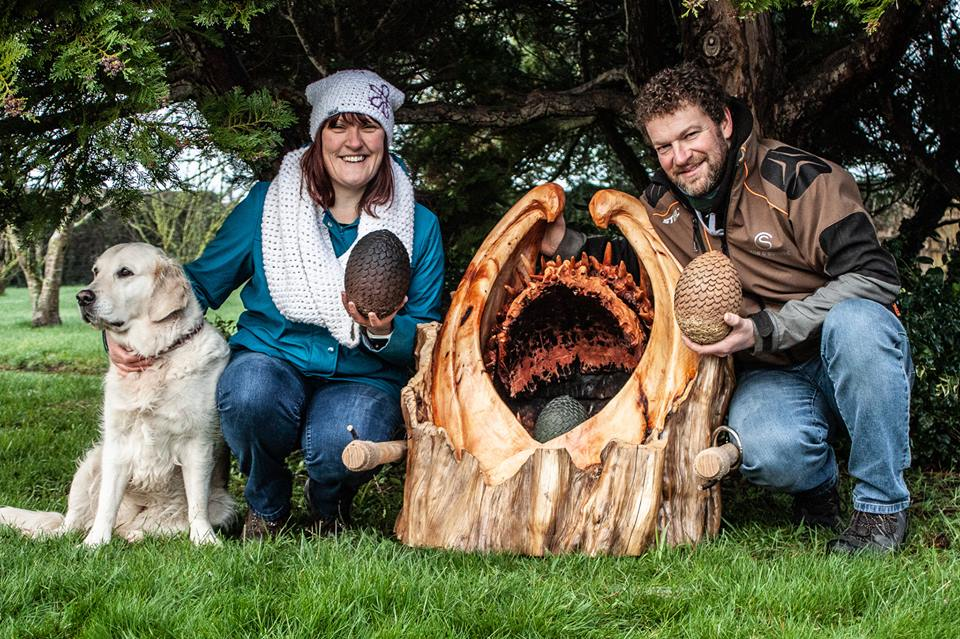 Artist simon o'rourke, his wife Liz and dog kneel either side of his game of thrones sculpture; a dragon-mouth egg casket