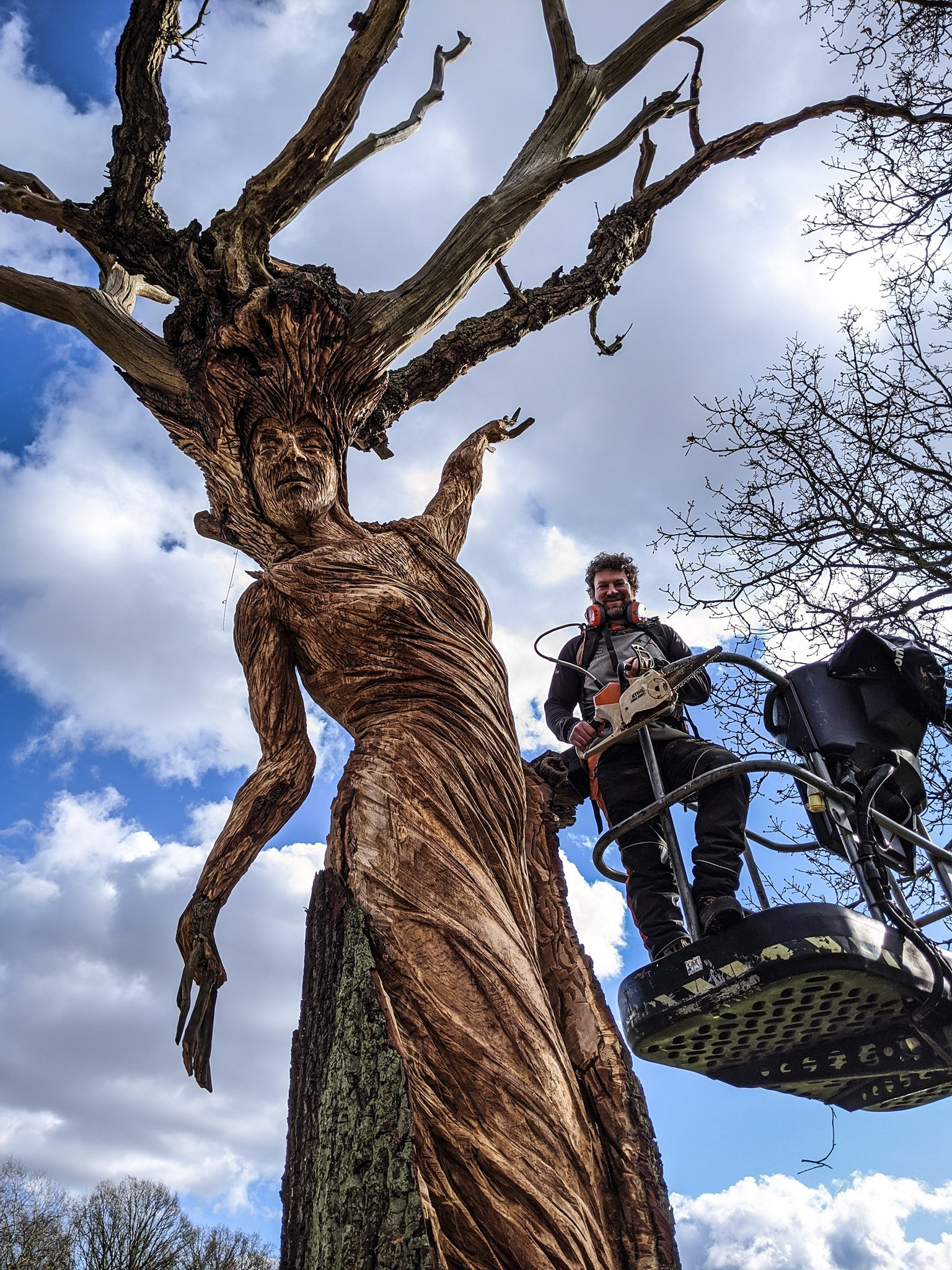 simon o rourke stands in a cherry picker next to the oak maiden sculpture he created in a dead oak tree. sculptures of 2020.
