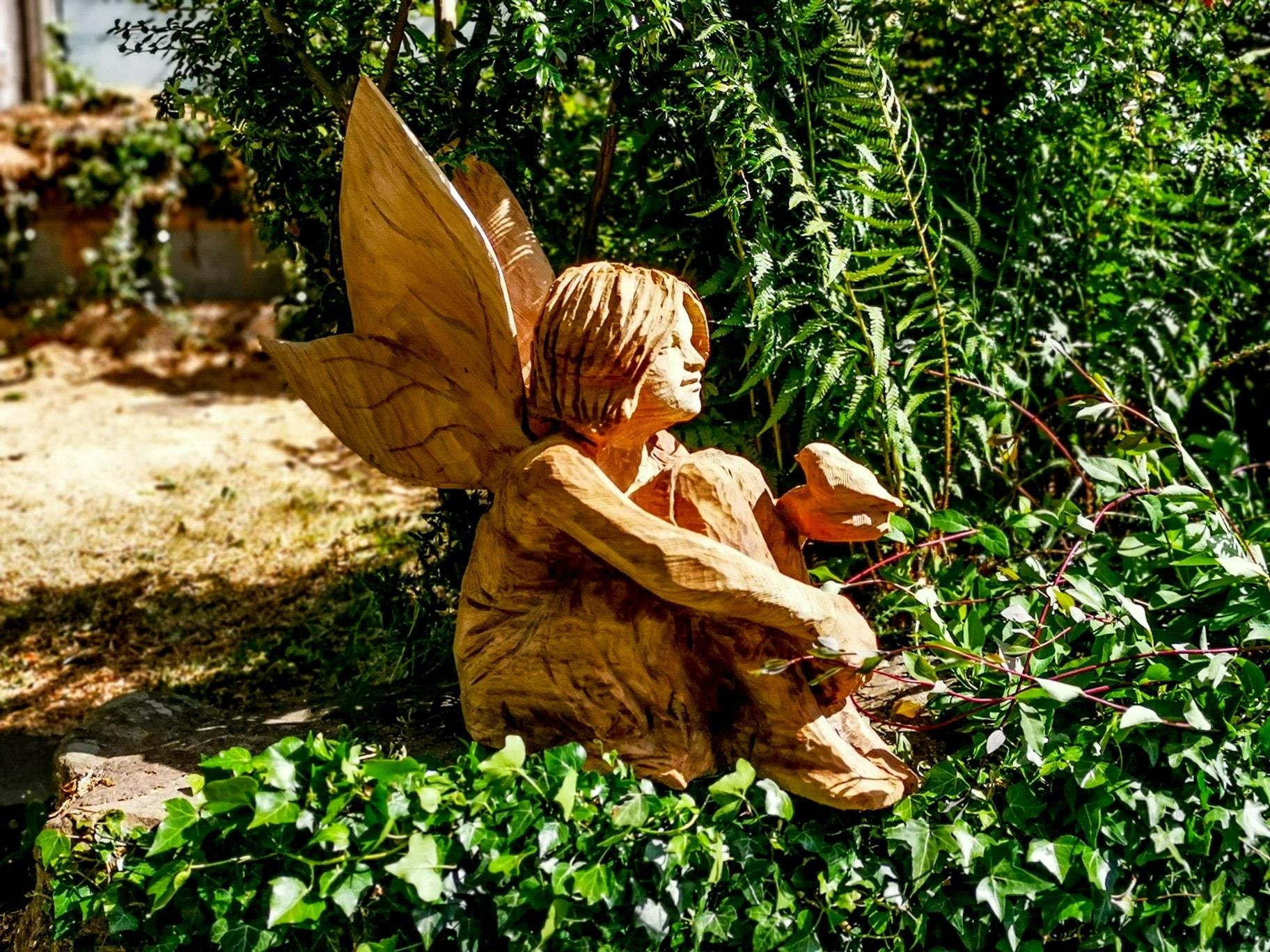 sculptures of 2020 by simon o'rourke. A girl is depicted as a fairy sitting surrounded by greenery. A robin sits on her hand as if in conversation with her.