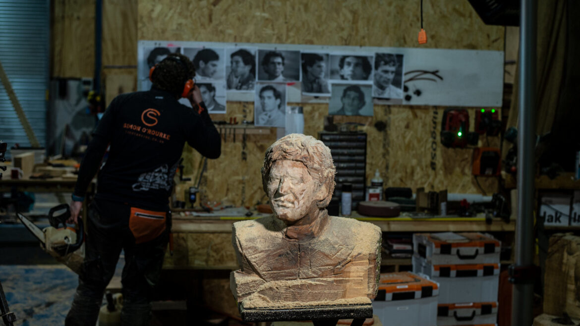 ayrton senna bust by simon o'rourke in foreground. It is in progress. In the background Simon looks at a wall of senna photos, checking the details for his sculpture