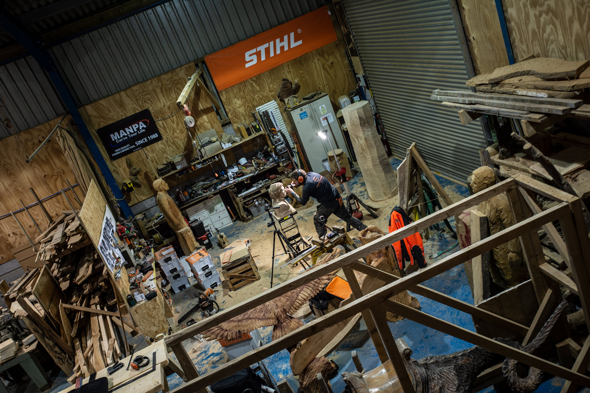 Why is art expensive? Simon O'Rourke is working on a sculpture in the middle of a busy workshop. Running the workshop, insurance, licensing for the chainsaw users etc are some of the costs behind his artwork