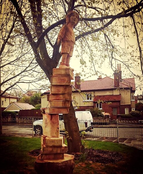 sculptures for world book day: learning to fly by Simon O'Rourke depicts a child about to soar standing on top of a tower of books