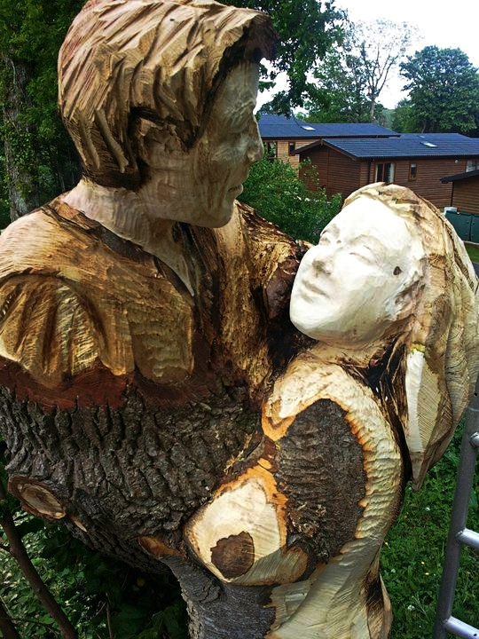 romeo and juliet carved into two intertwined tree trunks. It is one of Simon O'Rourkes romance-themed sculptures.