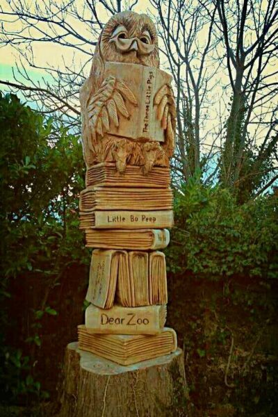Sculptures for world book day by Simon O'Rourke. An Owl sits on top of a tower of books in a 'totem pole' style sculpture.