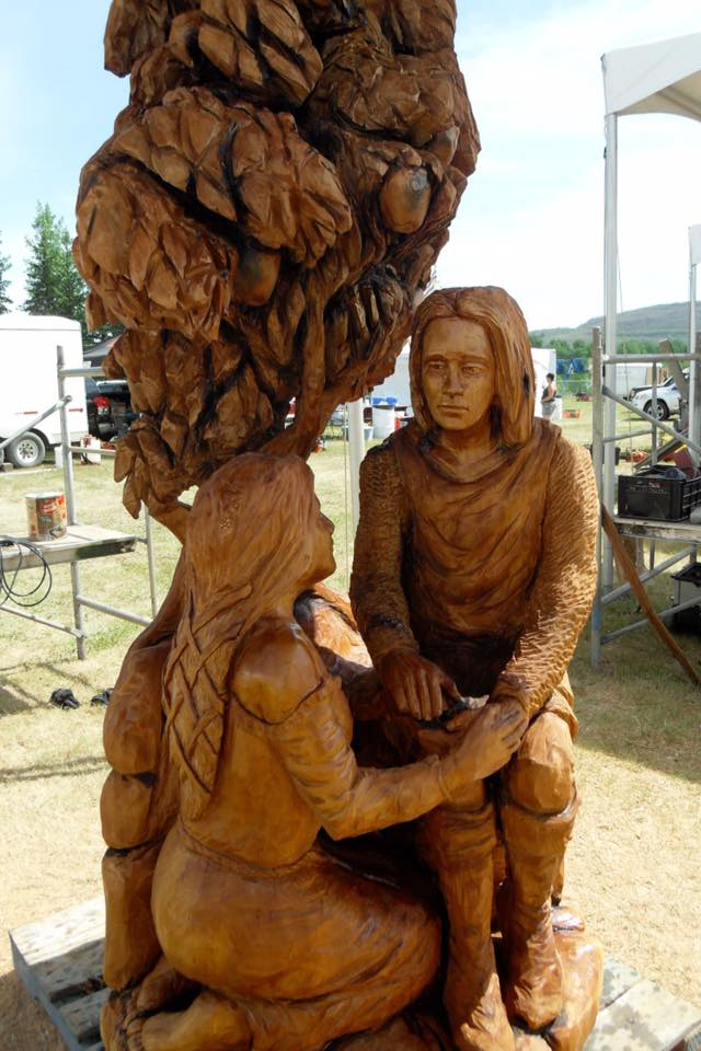 Romance-themed sculptures by Simon O'Rourke. a wooden sculpture of lancelot and guinevere. She kneels at his feet as he gazes into her eyes.