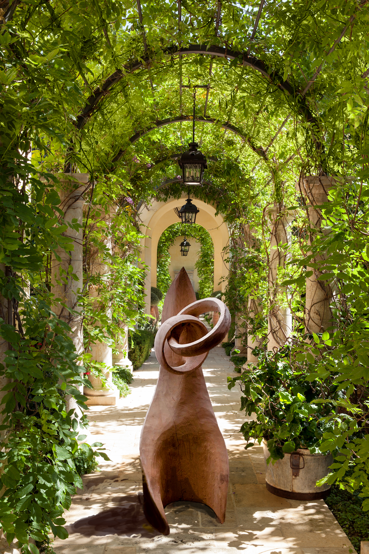 wooden wedding rings superimposed in an archway of greenery. Simon O'Rourke made the rings. They are part of his wooden wearables range.