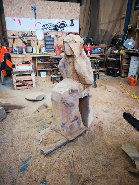 Photo shows a chainsaw carving workshop with a sculpture in progress in the middle. The shape of a female sitting on a swing is blocked out in a large piece of oak, but no features are visible