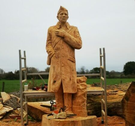 photo of a tree carving sculpture in progress. the sculpture is a wwi soldier in oak. there is a field and scaffolding behind him. the base of the sculpture shows the shape of the original tree trunk. the sculpture in in the front two thirds, and serves as an example of how to best position a sculpture within a log to avoid cracks that appear as it dries
