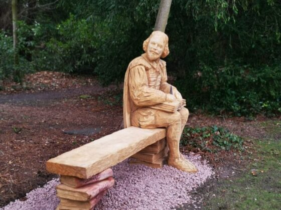 Photo shows an oak bench with a sculpture of shakespear sitting on the far end