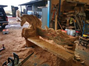 Tree carving workshop with a sculpture in progress. The sculpture is a bench, and one end is a horse with flame like mane