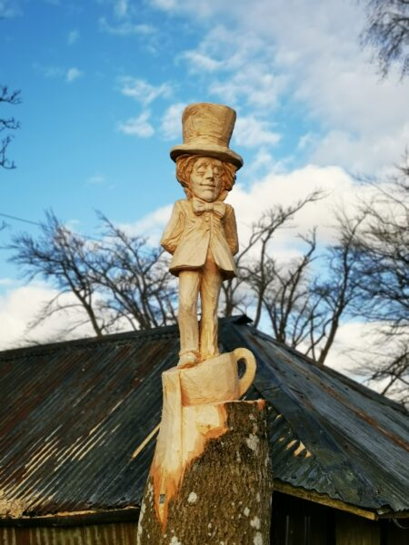 Panpurlais Mad Hatter sculpturte by Simon O'Rourke. Photo shows a view of the whole character with a metal barn roof behind