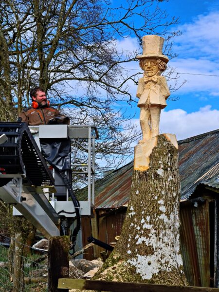 chainsaw artist simon o rourke stands in a cherry picker on the left. on the right is the sculpture he is working on - the pantpurlais mad hatter sculpture. the character is carved into a standing ash stump.