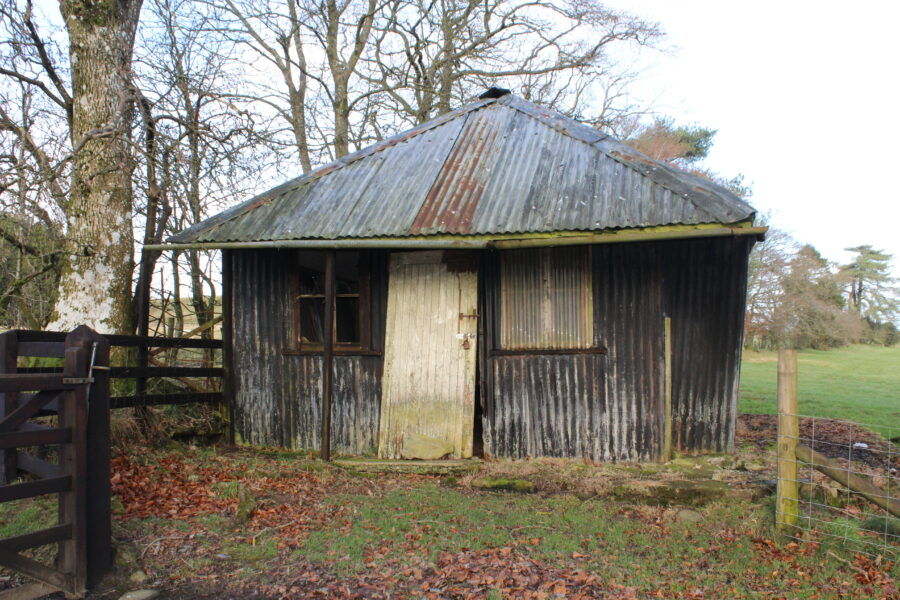Photo shows a derelict shed in a field with trees to its left. It is the former Pantpurlais teas rooms.