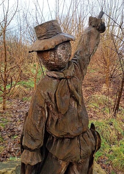 Sculpture of a scarecrow made from oak by Simon O'Rourke. He is pointing to the sky and surrounded by bare trees.