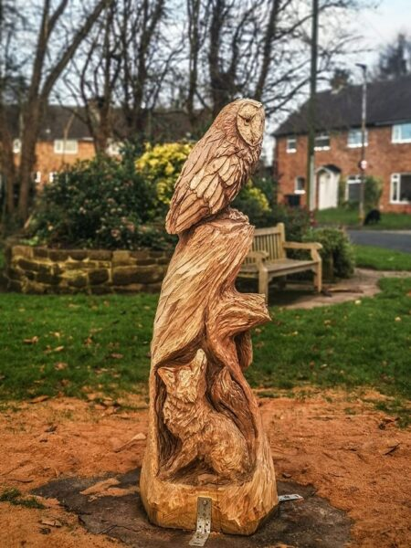 how to raise funds for your tree carving sculpture: this wildlife scene in capenhurst was funded by urenco. it features various local animals in a 'totem' style and is standing on a green space with houses in the background