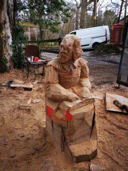 Bespoke shakespeare seat at poulton hall in procee. artist simon o'rourke has outlined Shakespeare in the wood sitting. It is clear it is a person but only his top half has any details.