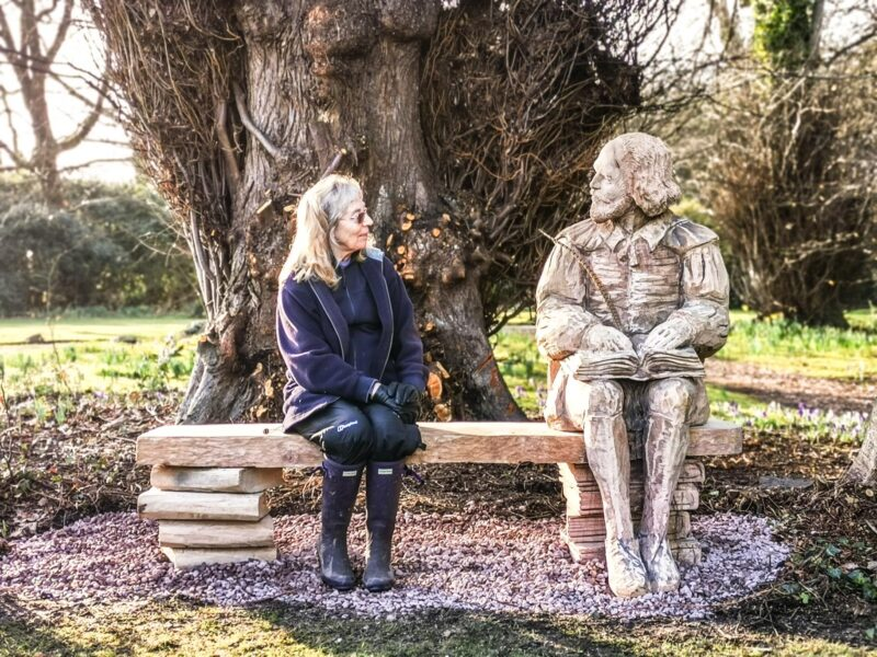 A client sits on on the bespoke shakespeare seat at poulton hall. It appears as if she is in conversation with a life size sculpture of William Shakespeare by Simon O'Rourke