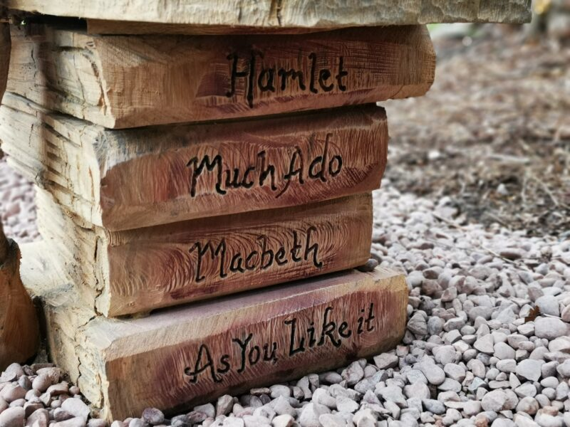 seat of a bench carved to look like a stack of books bearing titles of shakespeare plays. It is the leg of the bespoke shakespeare seat at poulton hall by simon o'rourke
