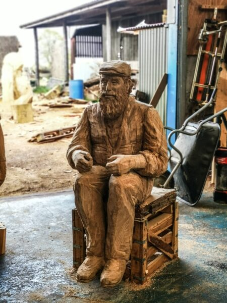Simon O'Rourke's Lews Castle Carriage driver sculpture photographed in his workshop. The sculpture is a lifesize cedar sculpture of a bearded man posed as if driving a pony carriage
