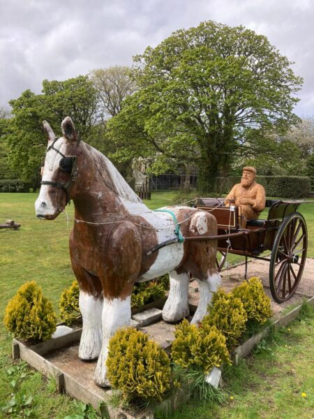 lews castle carriage driver sculpture by simon o'rourke. sculpture is seated in an antique pony cart being drawn by a wooden sculpture of a horse