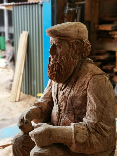 Close up of the face of simon o'rourke's cedar carriage driver sculpture