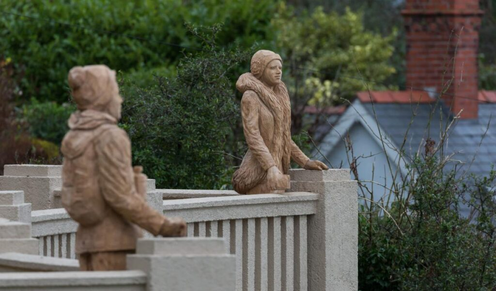 Two life size sculptures of women carved from oak, standing on a balcony at Prestatyn Hillside Shelter. They are two of Simon O'Rourke's public tree carving sculptures to see this bank holiday weekend