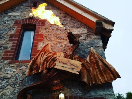 redwoos sculpture of dragon mounted on wall of a house. he is breathing fire.