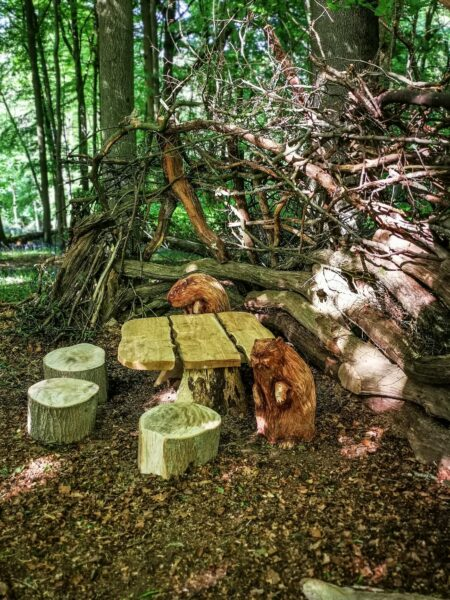 sideways view of the narnia beaver den sculptures by simon o'rourke. two beavers sit on tree trunk chairs around a table.