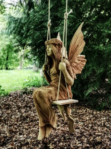whimsical fairy on a swing wood sculpture by chainsaw artist simon o'rourke