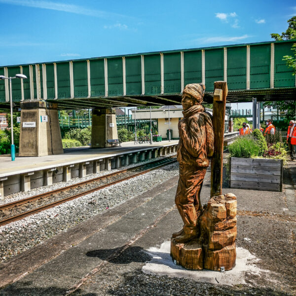 the prestatyn walker sculpture on the disused platform at Prestatyn Station. A railway bridge is visible in the background.