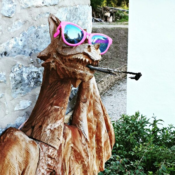 The Dragon Tower's Fire-Breathing Dragon wearing pink sunglasses. It's taken from an angle that makes him appear to recline in the sun