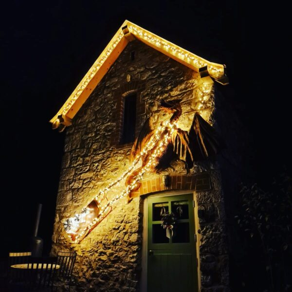 The Dragon Tower's Fire-Breathing Dragon at Christmas. He is pulling a sled and decorated with fairy lights