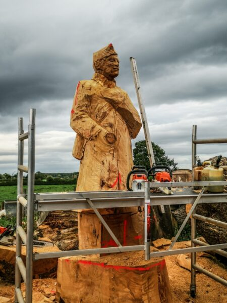 Life size wood sculpture of a WWI soldier in progress. There is scaffolding in front of him, and three chainsaws sit around