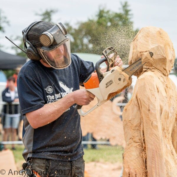 Tips for chainsaw carving in the sun. Photo shows simon o'rourke wearing protective headgear, carving a female sculpture from wood using a stihl chainsaw.