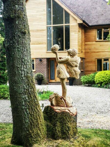 Oak fairy sculpture entitled 'the offering' by simon o'rourke
