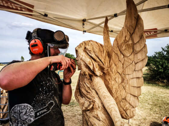 tips for chainsaw carving in the sun: wear a powered air filter mask so it passes air across your face. in the photo simon o'rourke is carving an angel wearing such a mask.