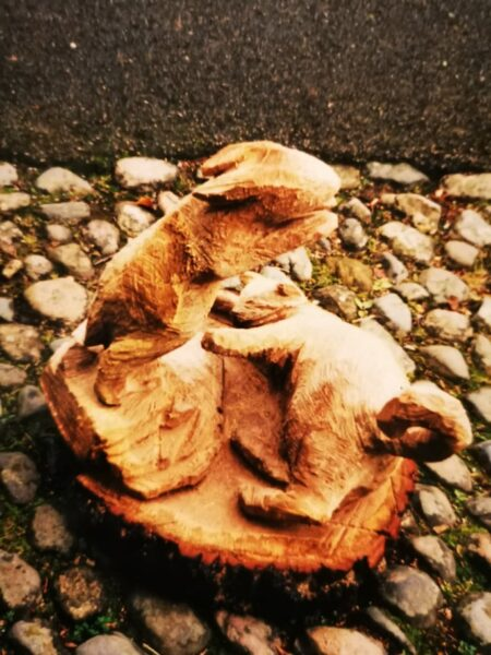 chainsaw carving of a rabbit jumping over a cat