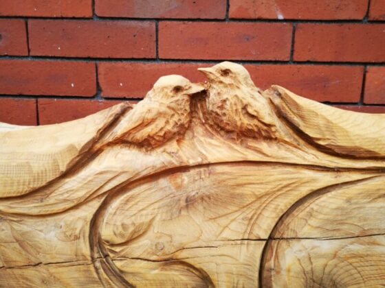 close up of a pair of robins carved into a cedar bench.