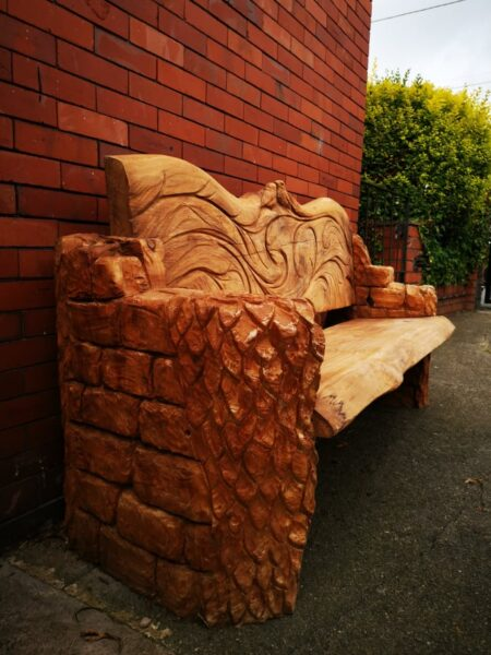 close up of the sides of robin memorial bench by simon o'rourke. the sides are created to look like brick with ivy growing up them
