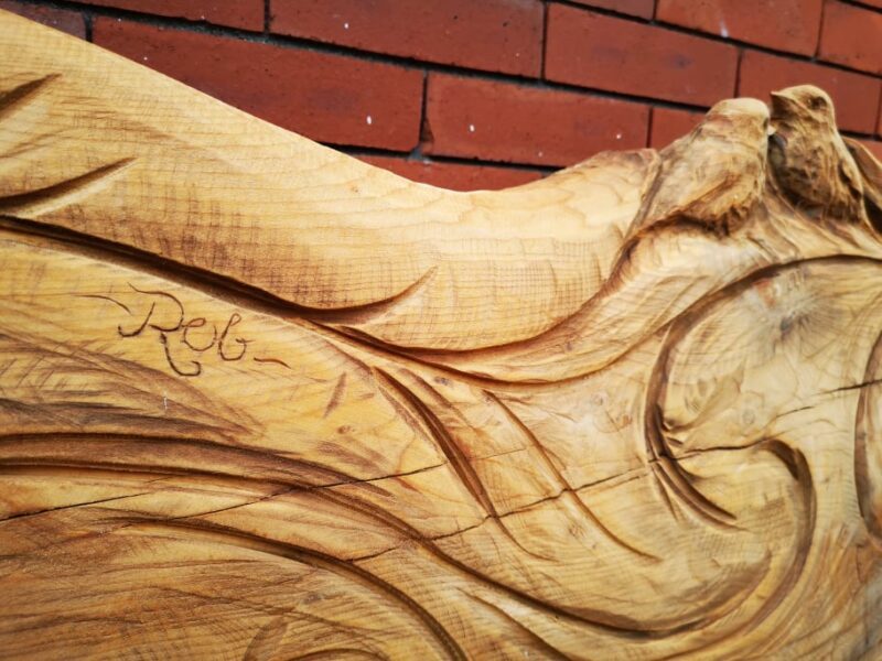 the name 'rob' is carved into the back of a cedar bench featuring two robins on the back. it is part of the robin memorial bench created by chainsaw artist Simon o'rourke