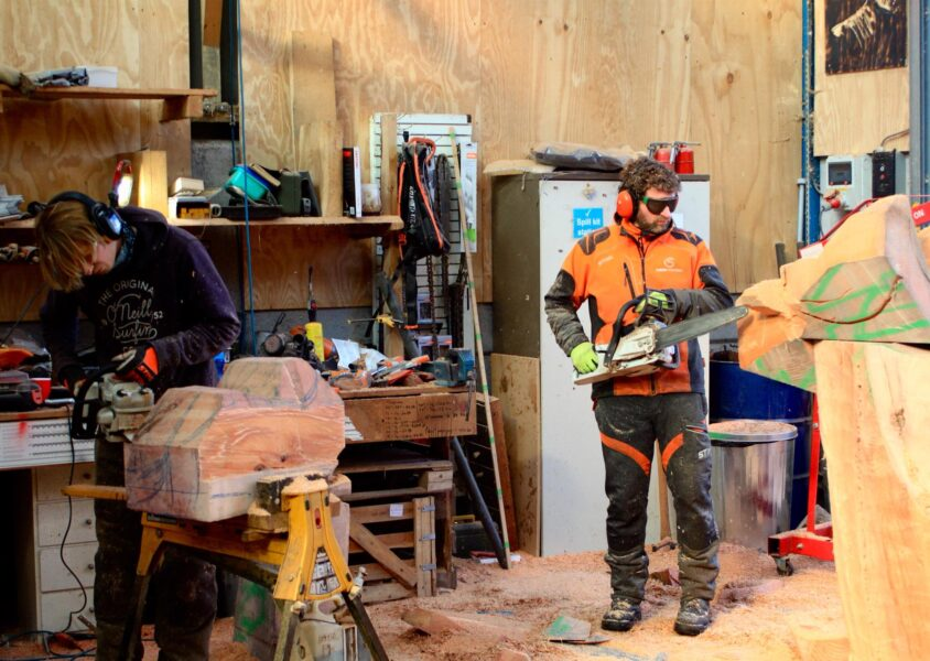 Chainsaw artist Simon o'rourke and his apprentice Paul Ossum in a workshop creating a sculpture trail with chainsaws.