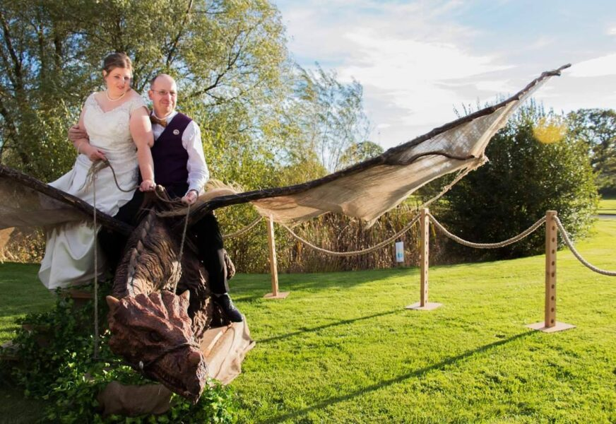 a couple in wedding attire sit on a chainsaw carved dragon