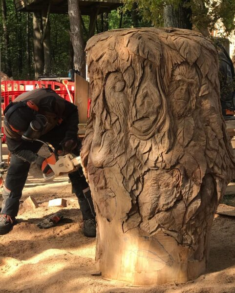 Simon o'rourke working on a carved throne with jungle patterns at zandsculpturenfestijn, one of his top chainsaw carving events